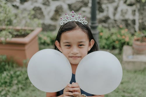 Girl Wearing A Crown Holding Two White Balloons
