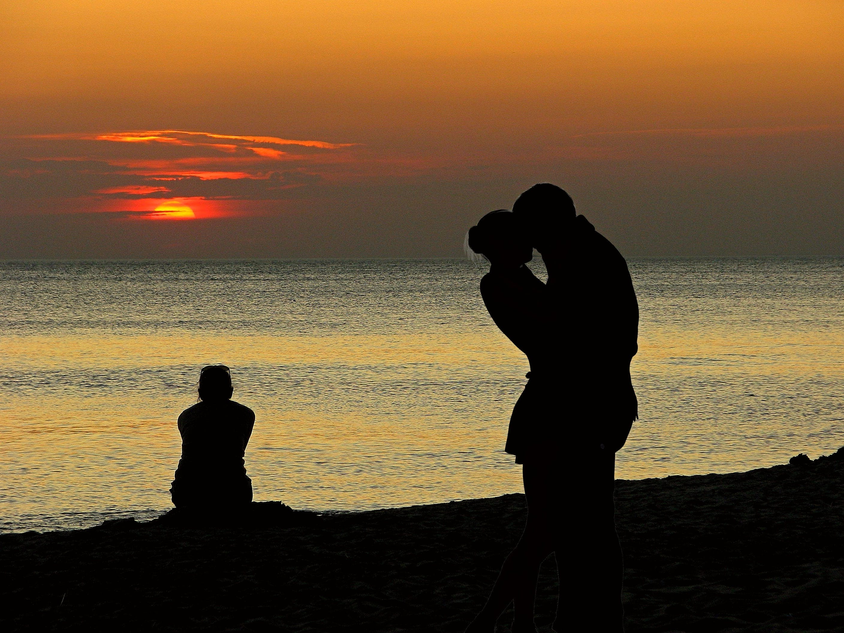 Silhouette Photography of Couple About to Kiss Near on Body of Water