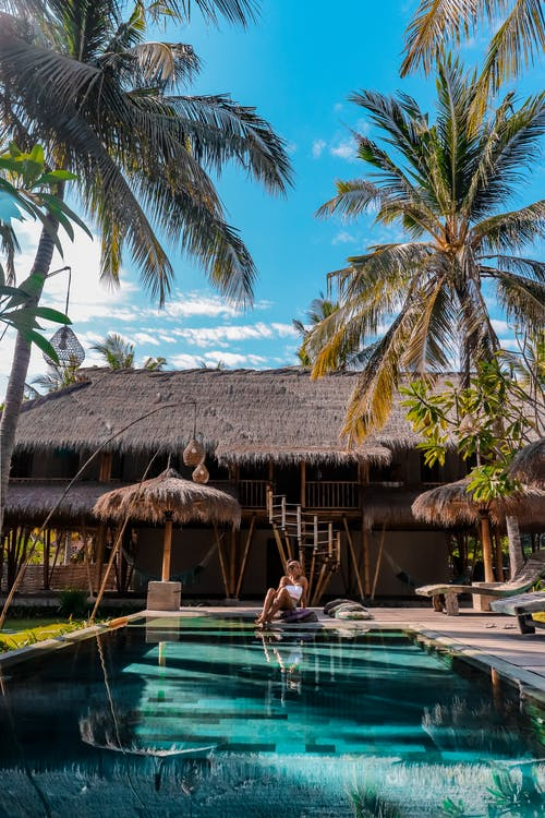 Woman Sitting Beside Pool in Front of Thatch Roofed Building