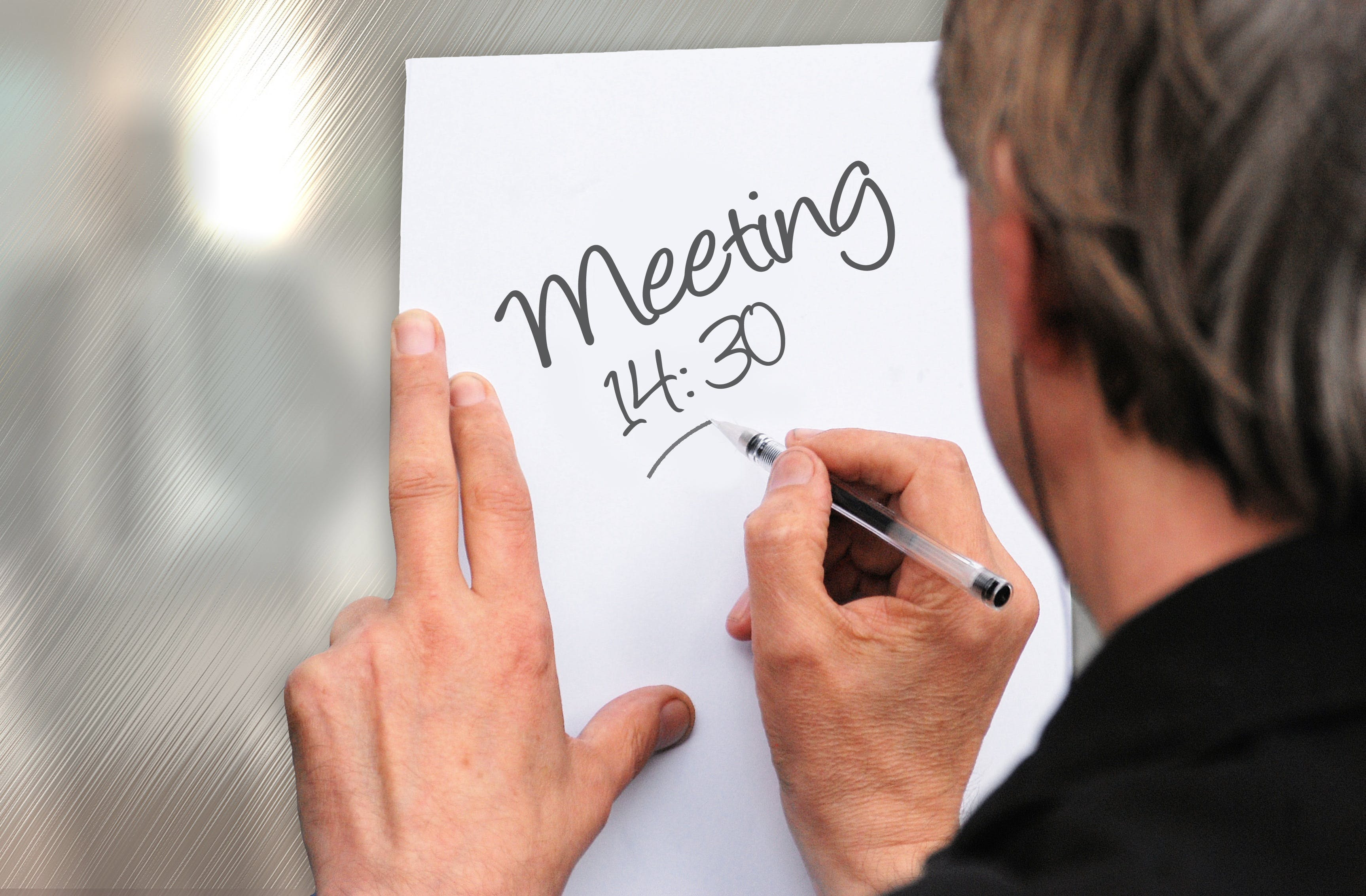 Man Writing on Meeting 14:30 on Paper