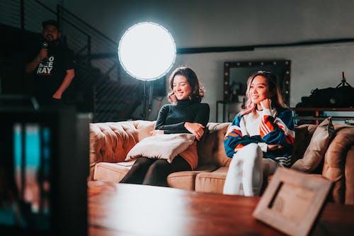Photo of Two Women Sitting on Sofa