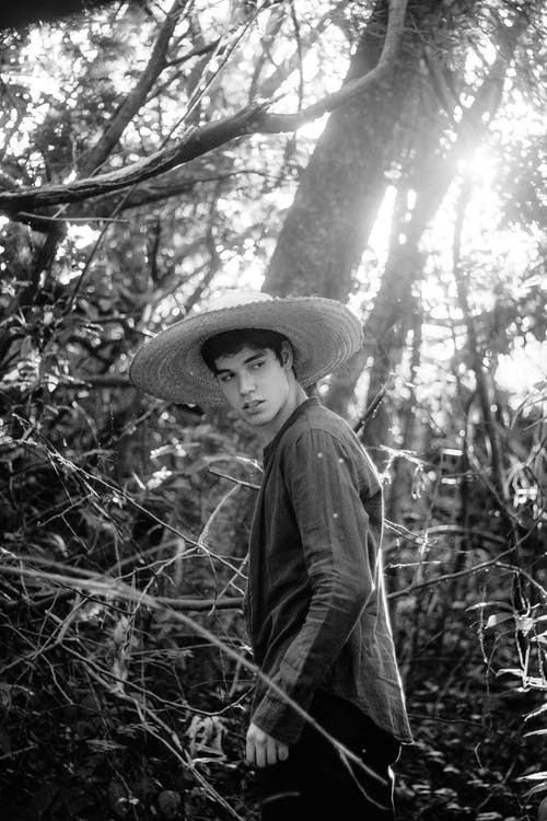 Grayscale Photo of Man in Straw Hat Standing in the Middle of the Woods