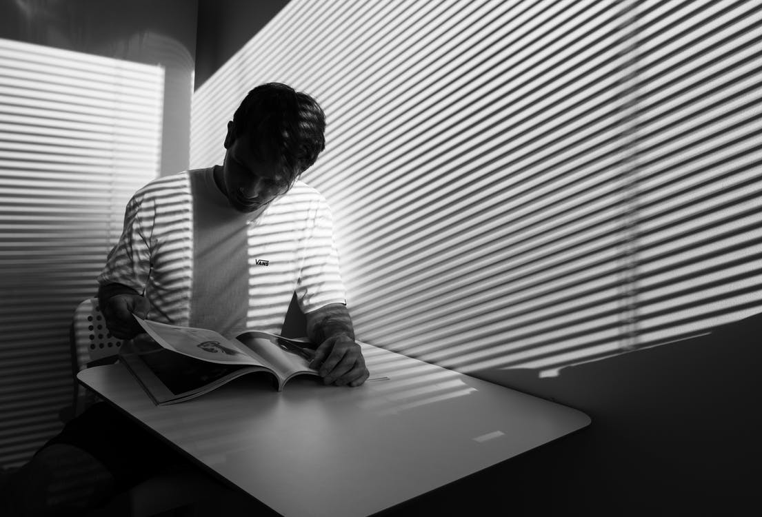 Grayscale Photography of a Man Reading Book