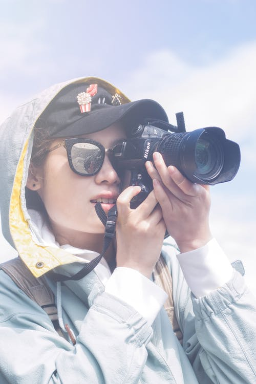 Photo of Woman in Hooded Jacket, Cap, and Sunglasses Taking a Picture Using a Black Nikon Dslr Camera