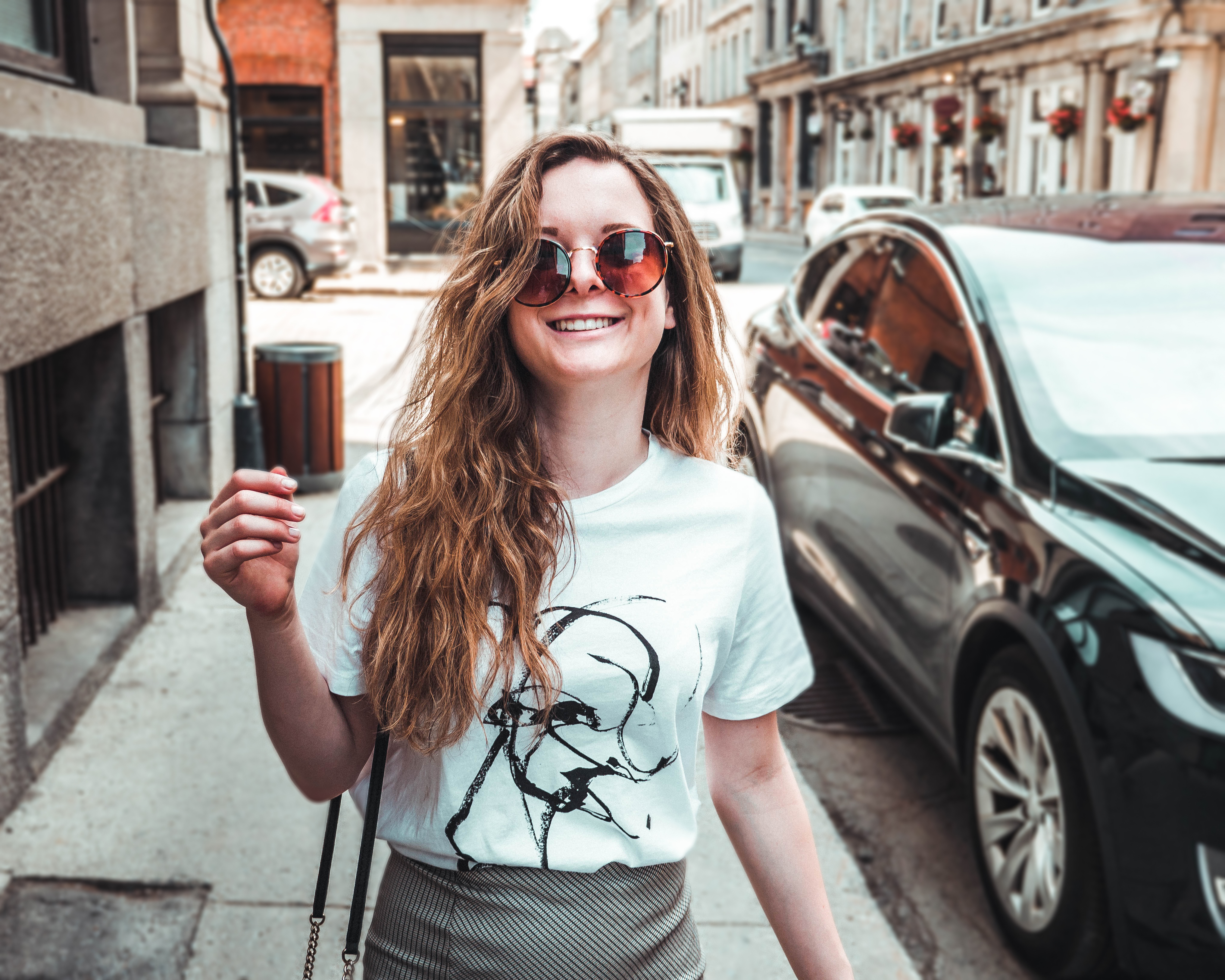 Photo of Smiling Woman in White T-shirt and Sunglasses Walking on Side Walk