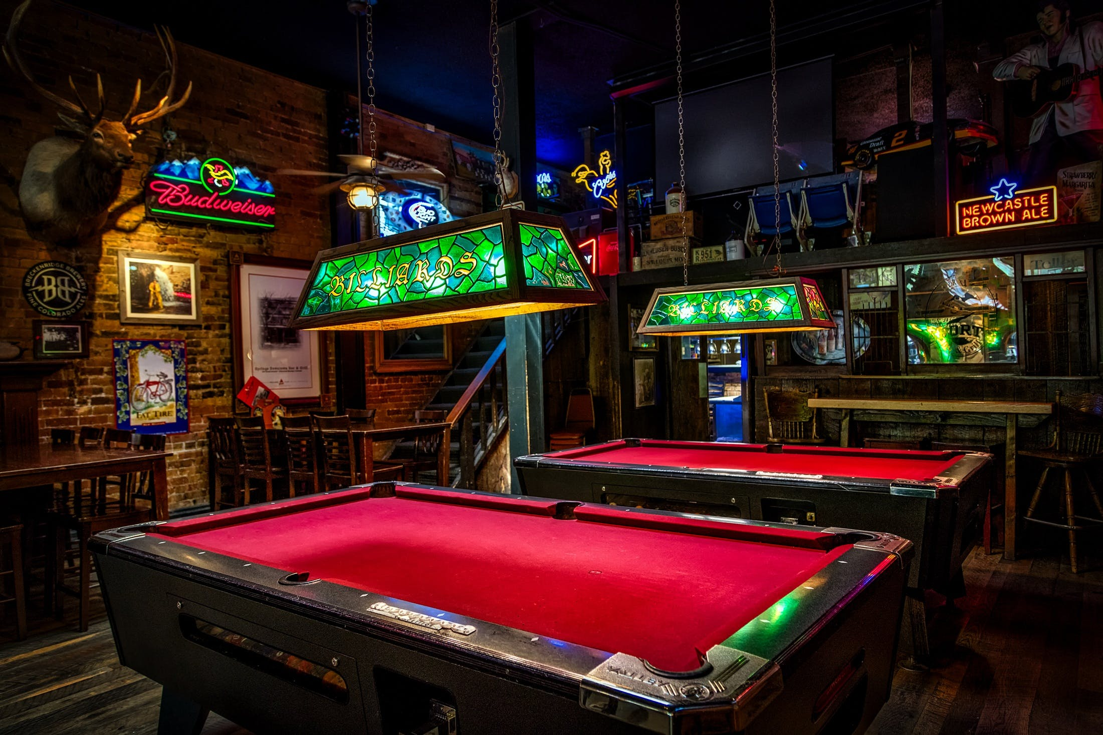 Brown and Red Billiards Tables With Green Lamps