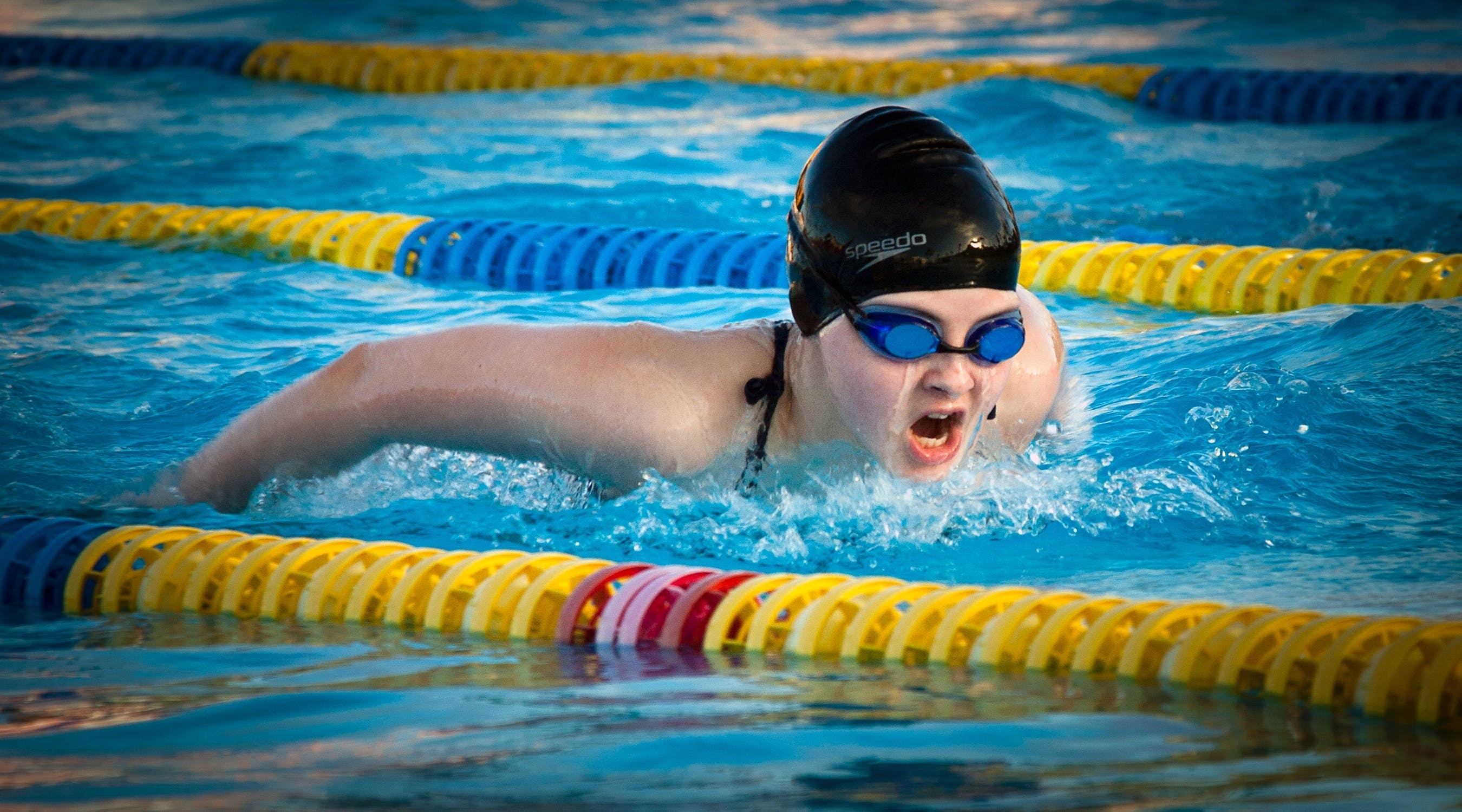 Woman Wearing Goggles Swimming on Pool