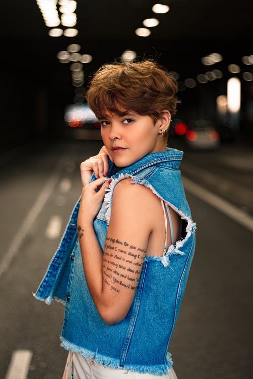 Selective Focus Side View Photo of Tattooed Woman in Blue Denim Vest Posing in the Middle of the Road