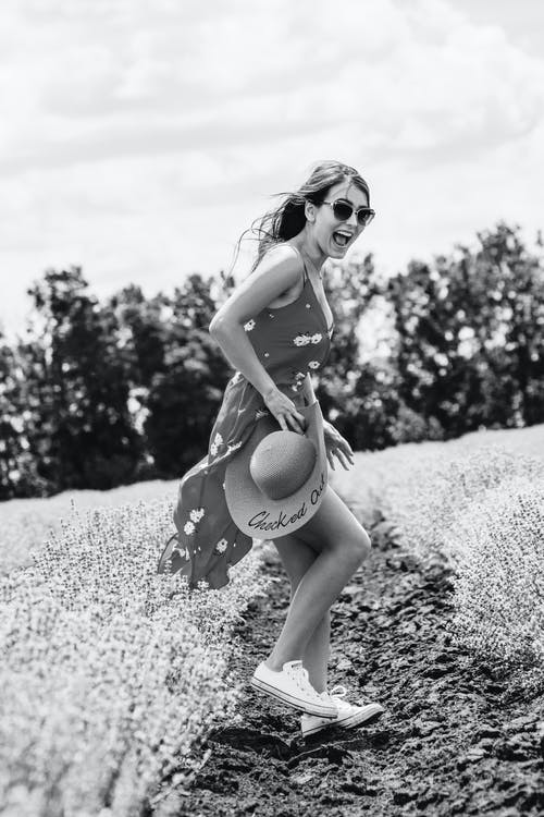Side View Grayscale Photo of Laughing Woman Floral Dress Standing in Flower Field Posing