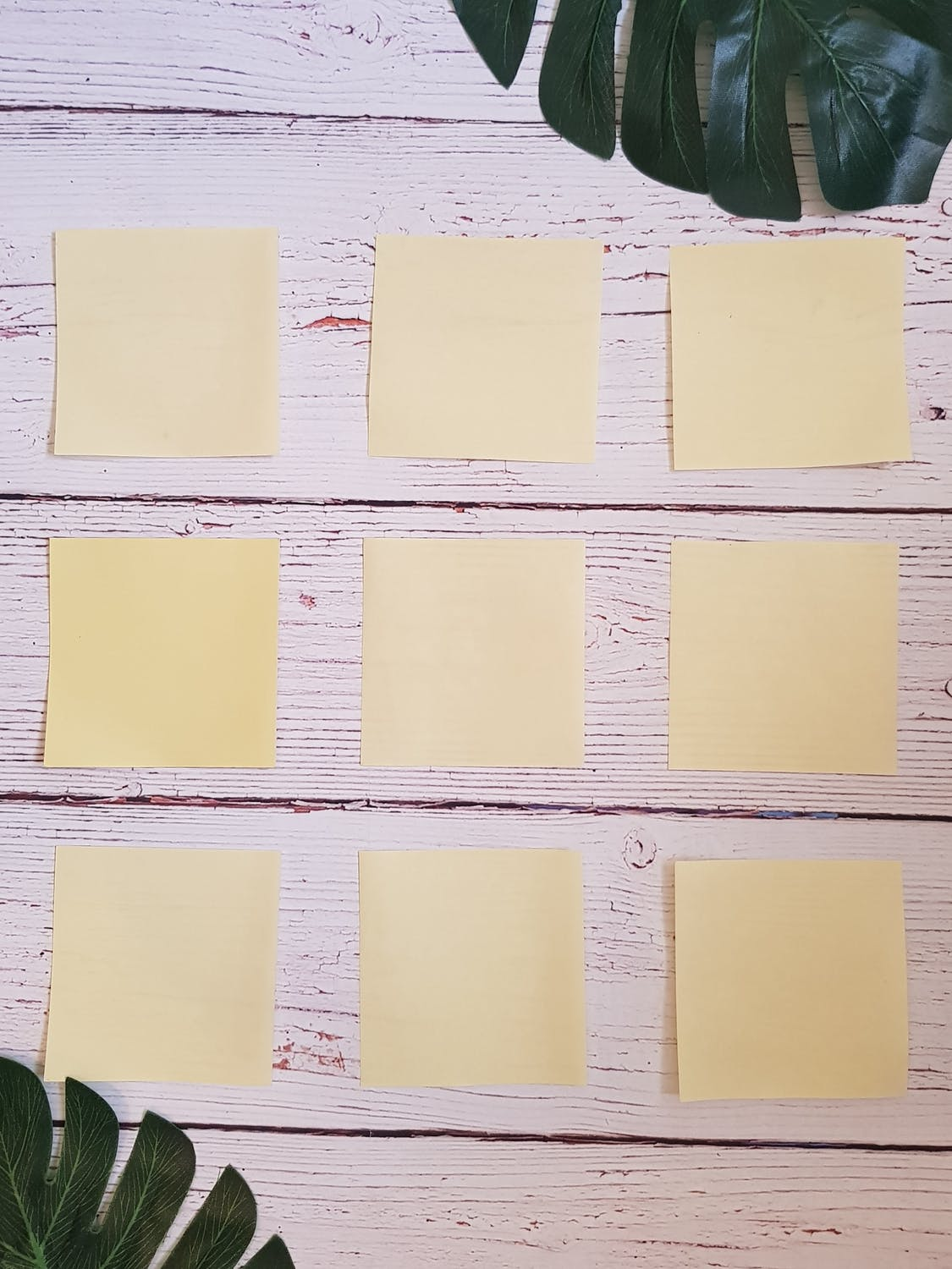 yellow sticky notes on distressed white wood surface