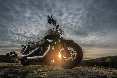 Low Angle Photo of Black Harley Davidson Forty-Eight 1200 Motorcycle Parked on Dirt Road During Golden Hour