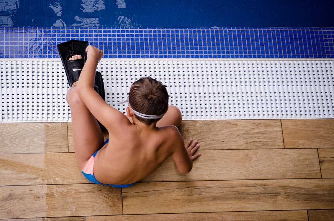 Boy Sitting Near Swimming Pool