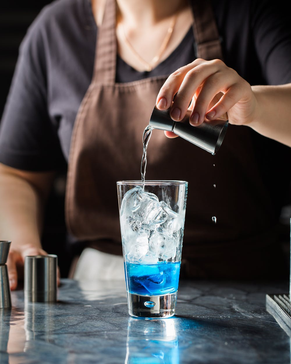 Bartender mixing drinks | Photo: Pexels