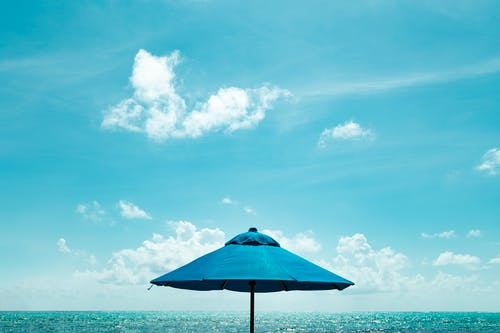 Close-up Photo of Blue Parasol Near Body of Water Under Blue Sky