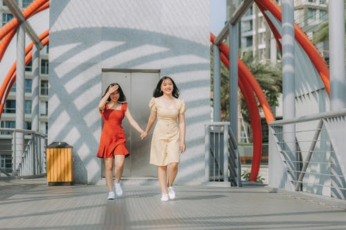 Photo of Two Smiling Women Walking While Holding Hands