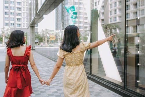 Photo of Two Women Holding Hands While Walking