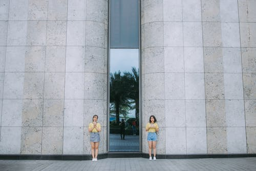 Two Women Standing Beside Brown Concrete Building
