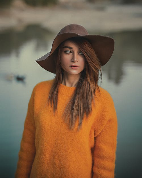 Photo of Woman in Orange Sweater and Brown Hat Posing While Looking Away with Body of Water in the Background
