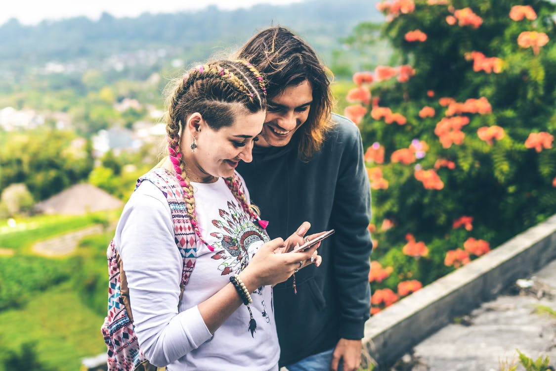 Photo of Man and Woman Smiling Looking at Mobile Phone