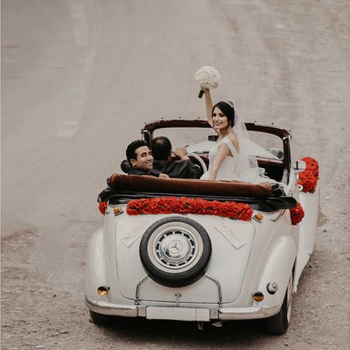Groom And Bride Riding On White Vehicle