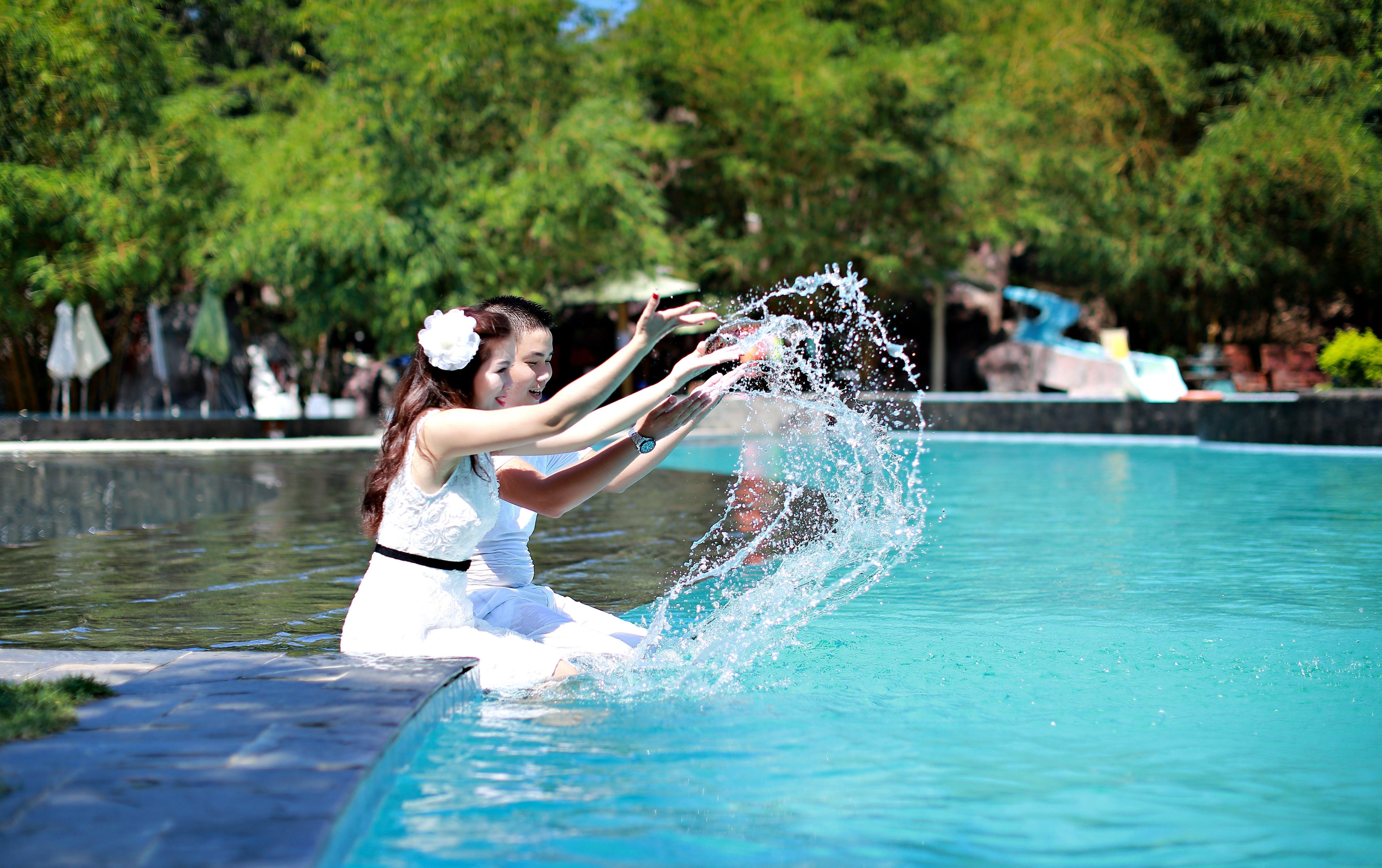 Woman and Man Sitting on Swimming Pool While Playing Water Splash