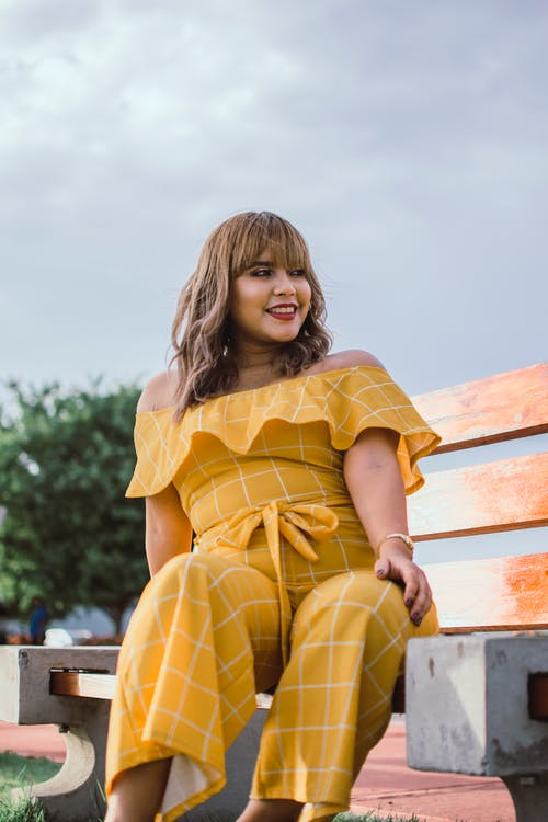 Photo of Smiling Woman in Yellow Jumpsuit Sitting on Wooden Bench Posing While Looking Away