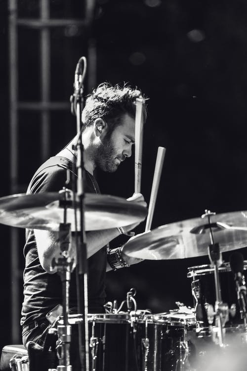 Grayscale Photo of a man playing drums