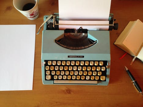 A bluish typewriter with a paper rolled into it with a cup of coffee, paper and pencil beside it