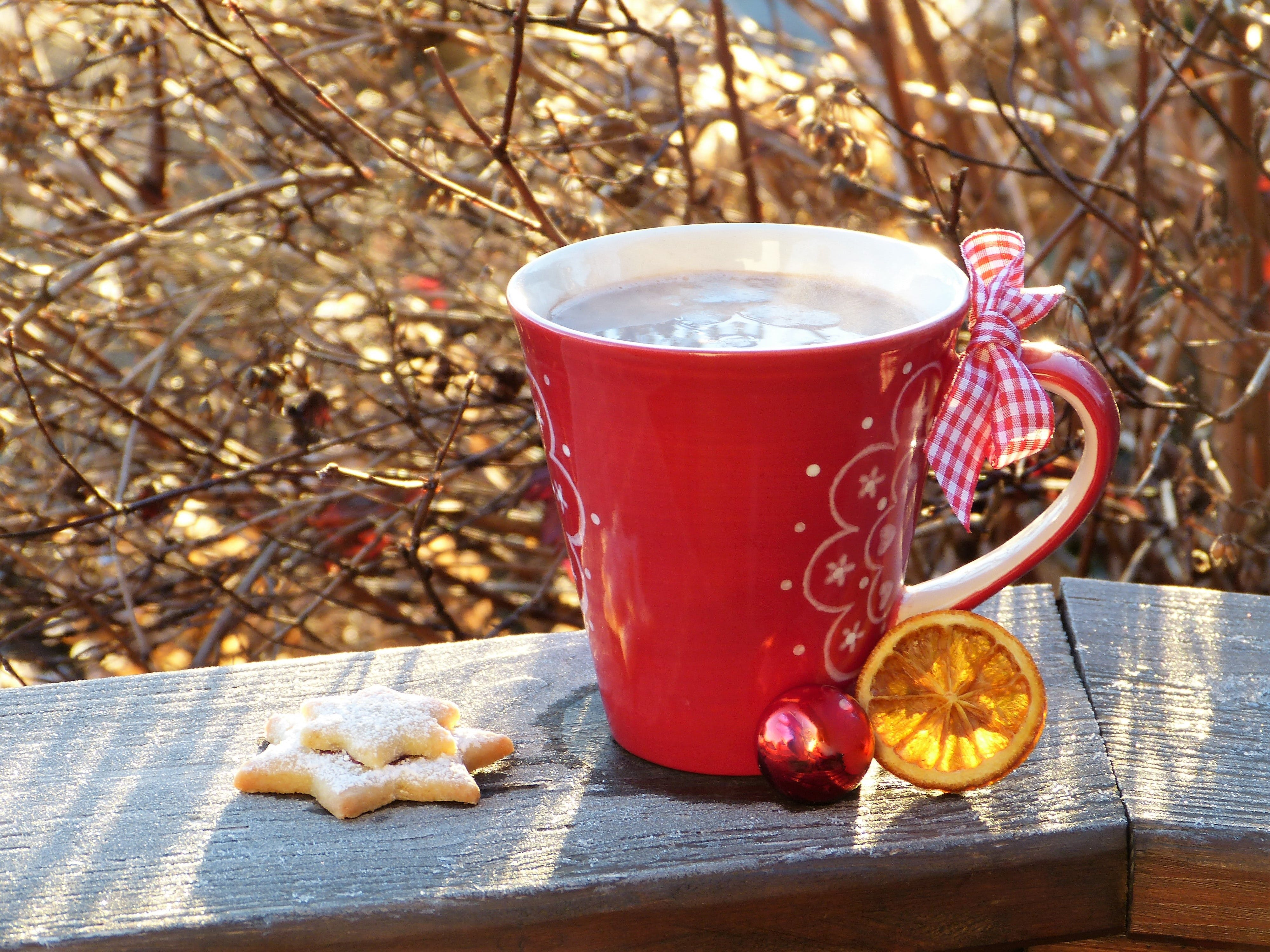 Red Ceramic Mug Beside Cookie on Brown Wooden Surface