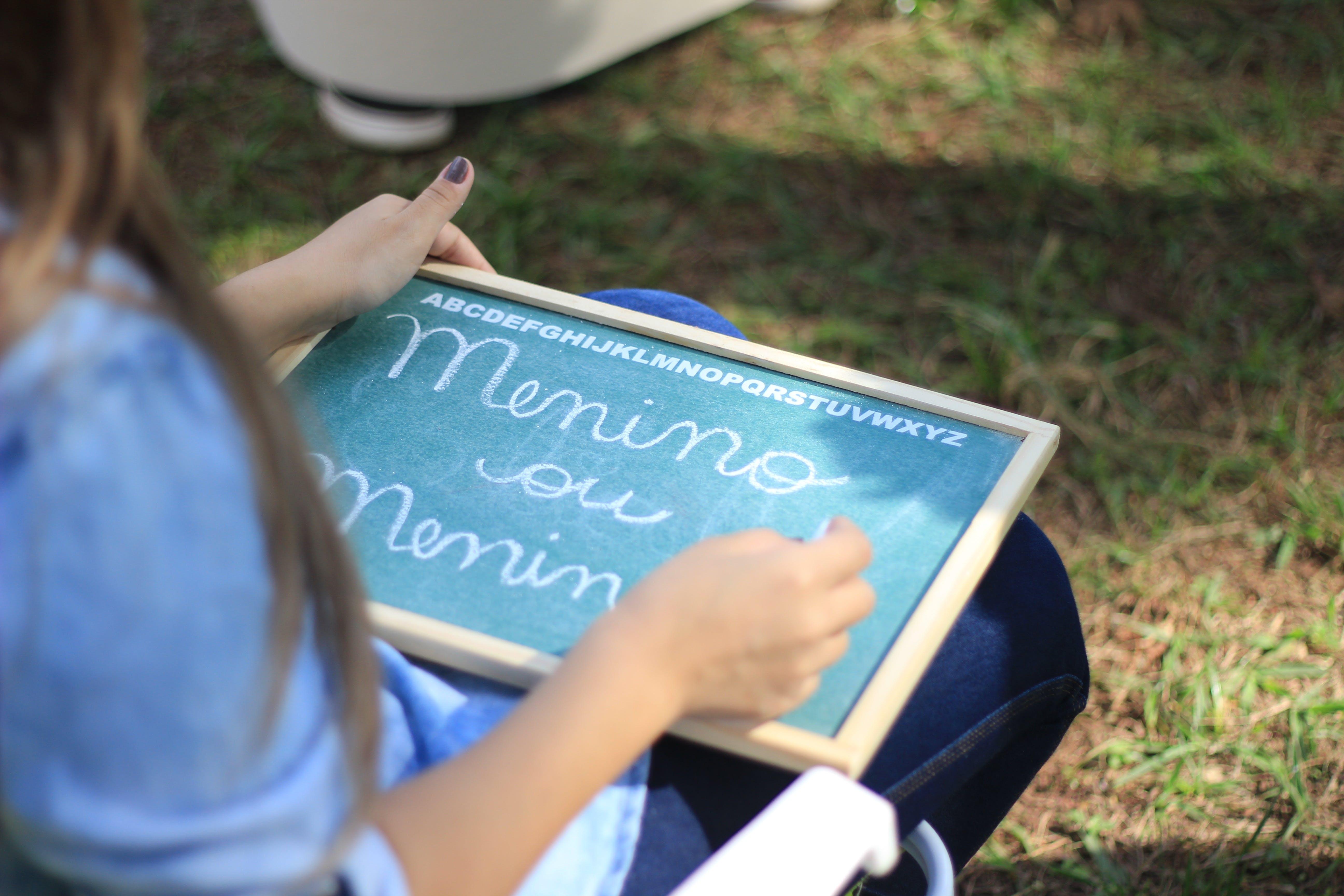 Woman Writing on Chalkboard