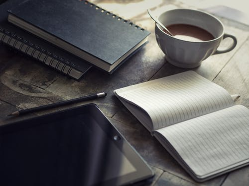 Flat Lay Photography of Books, Black Ipad, and Coffee Cup