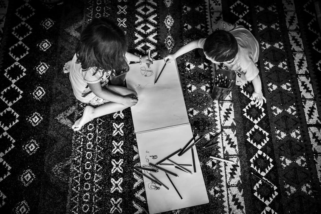 Two Toddler's Writing on a Sketch Pad