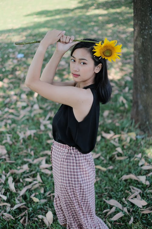 Photo of Woman Holding Sunflower