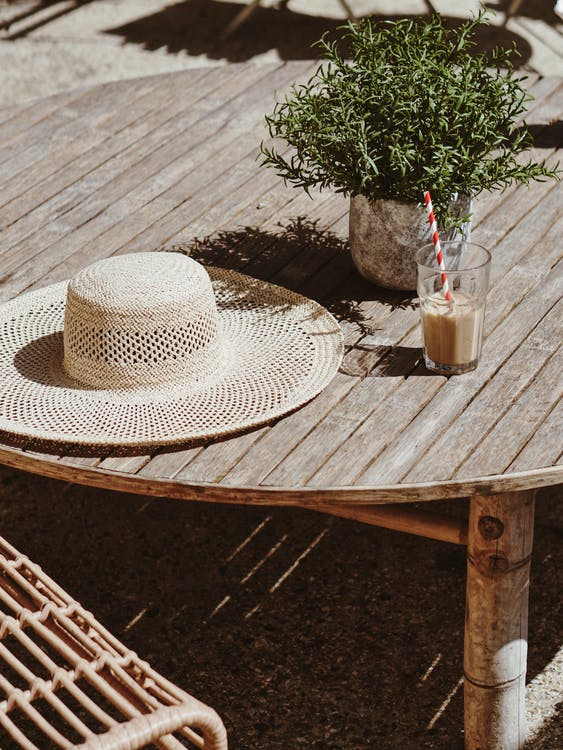 Hat Beside Green Leafed Plant On Table