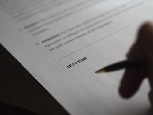 Person Holding Pen Near White Printer Paper