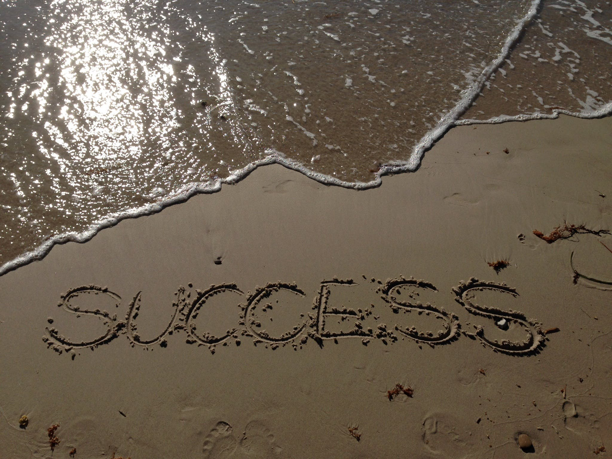 Success Text Write on Beach Shore