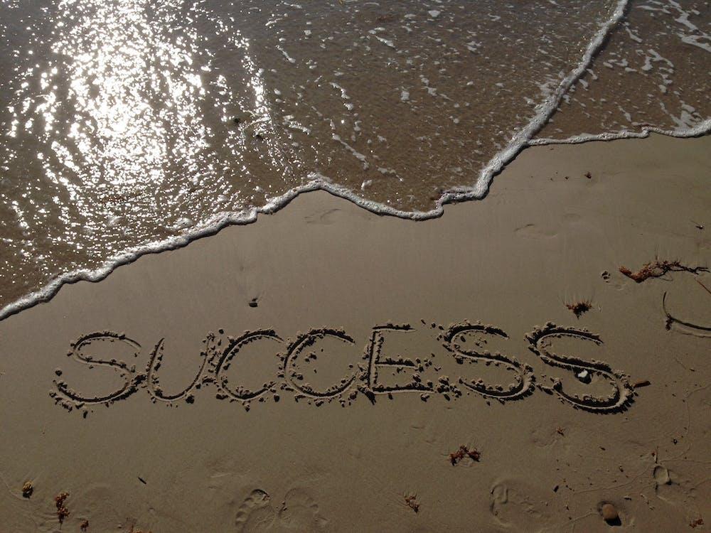 Success Text Write on Beach Shore