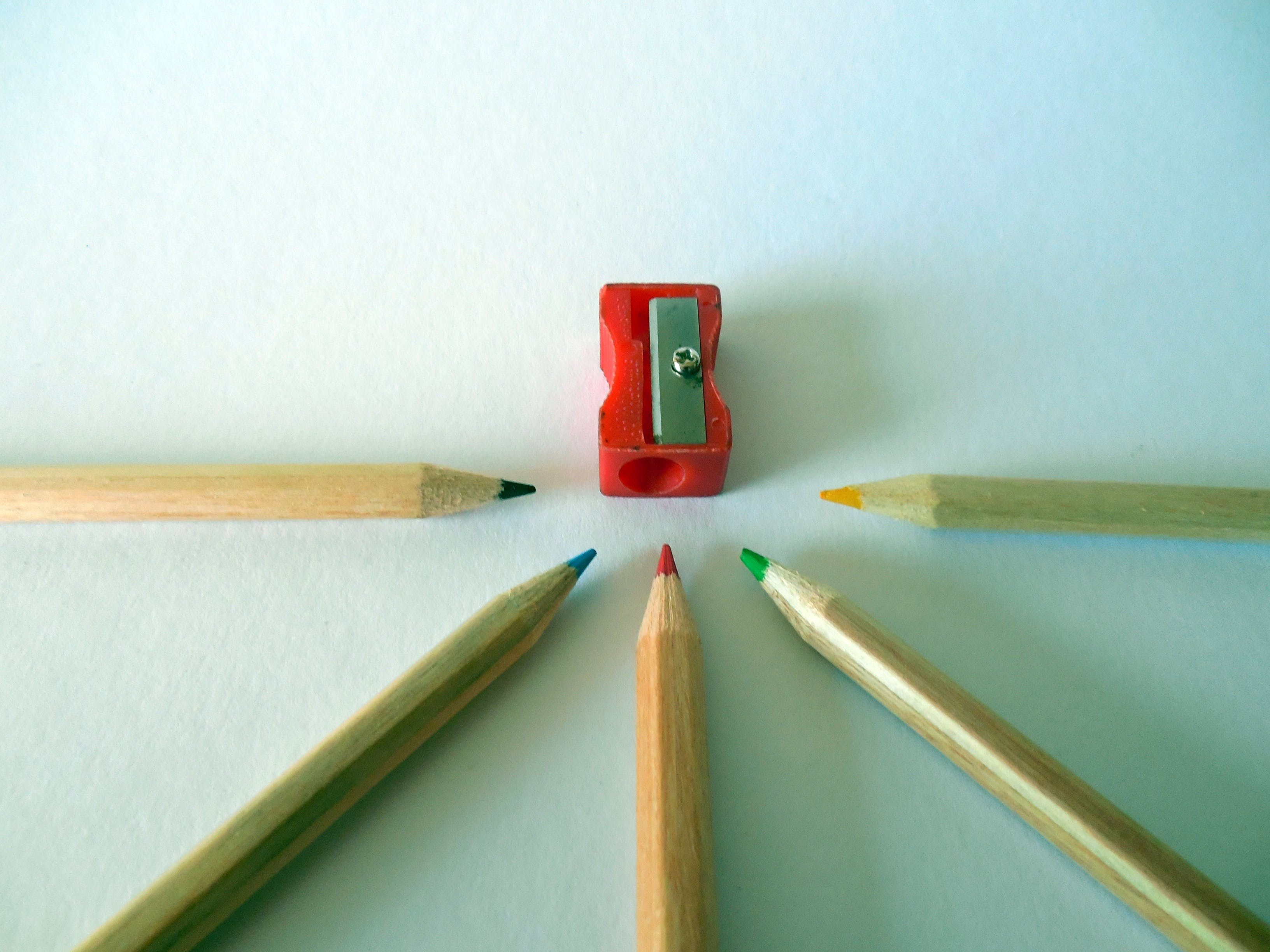 Flat Lay Photography of Red Pencil Sharpener With Four Colored Pencils