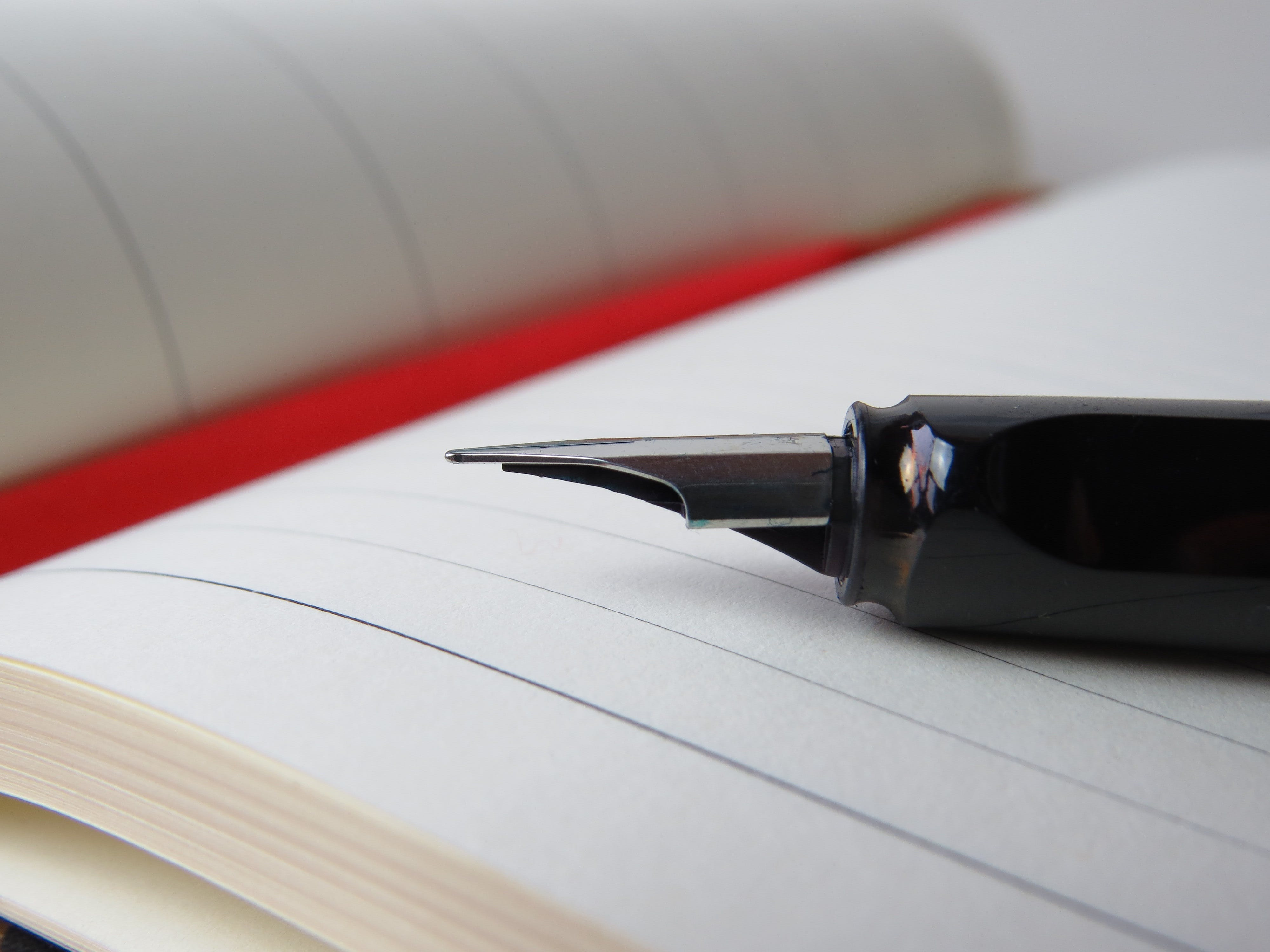 Selective Focus Photography of Calligraphy Pen Placed on Top of Open Notebook