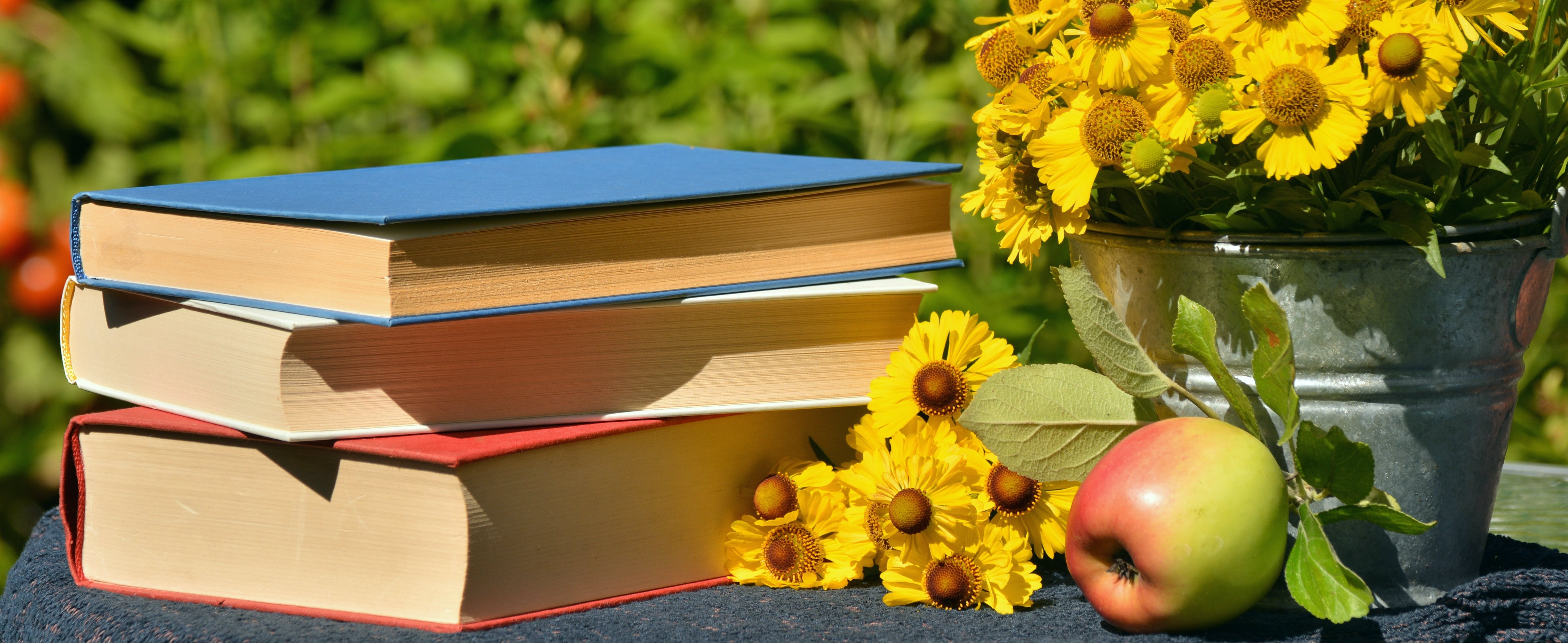 Three Books Beside Yellow Bouquet of Flowers