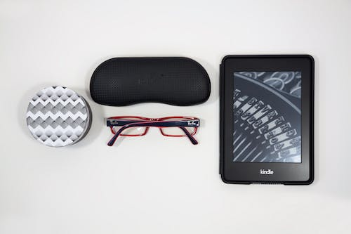 Flat Lay Photography of Eyeglasses and Amazon Kindle E-reader