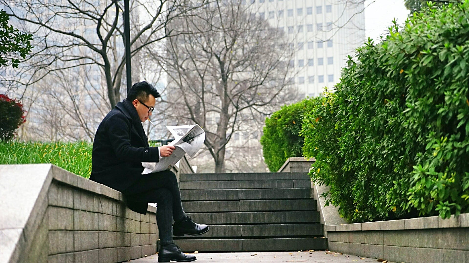 Man Reading Newspaper Sitting on Stair Wall