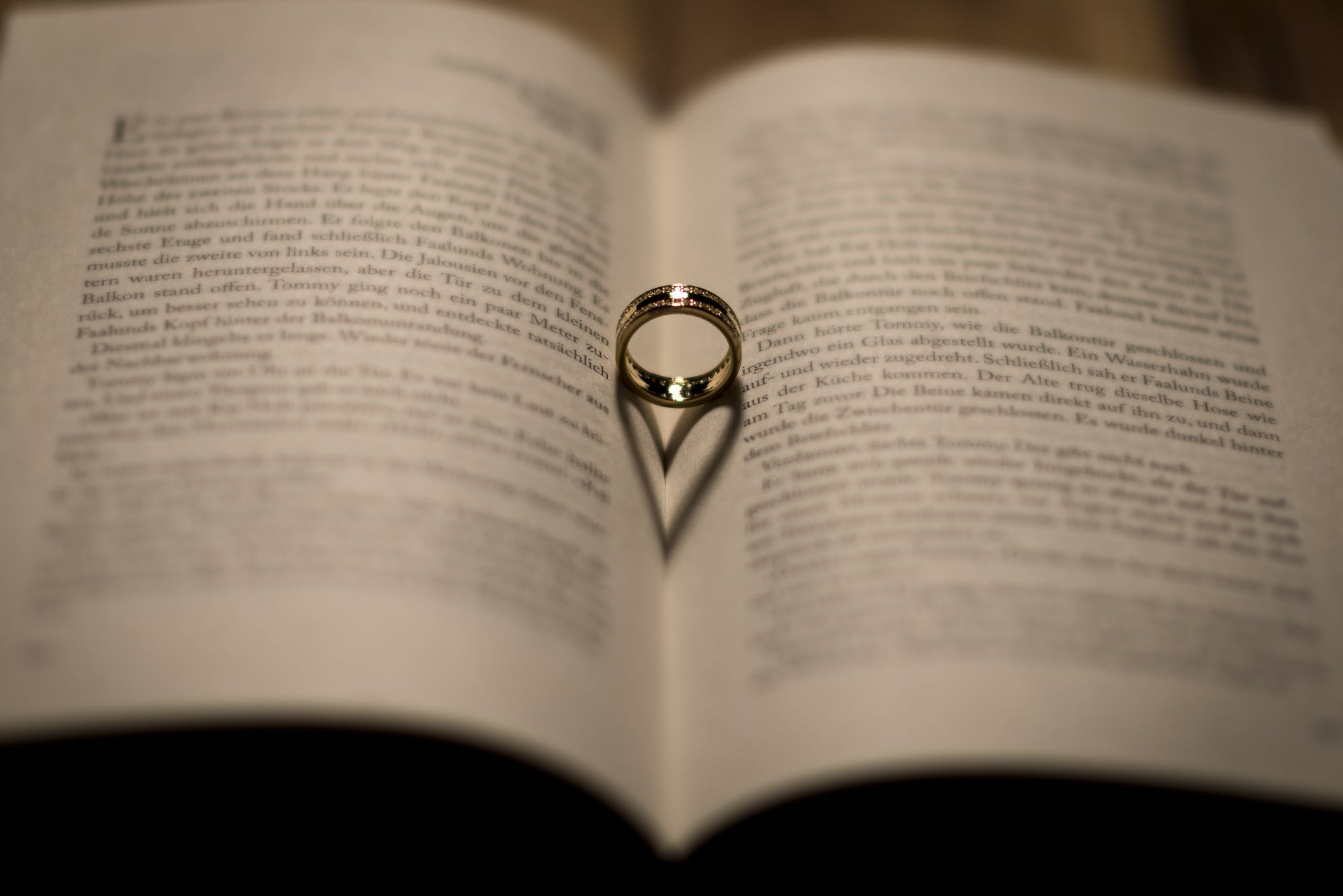 Selective Focus Photography of Silver-colored Ring on Opened Textbook