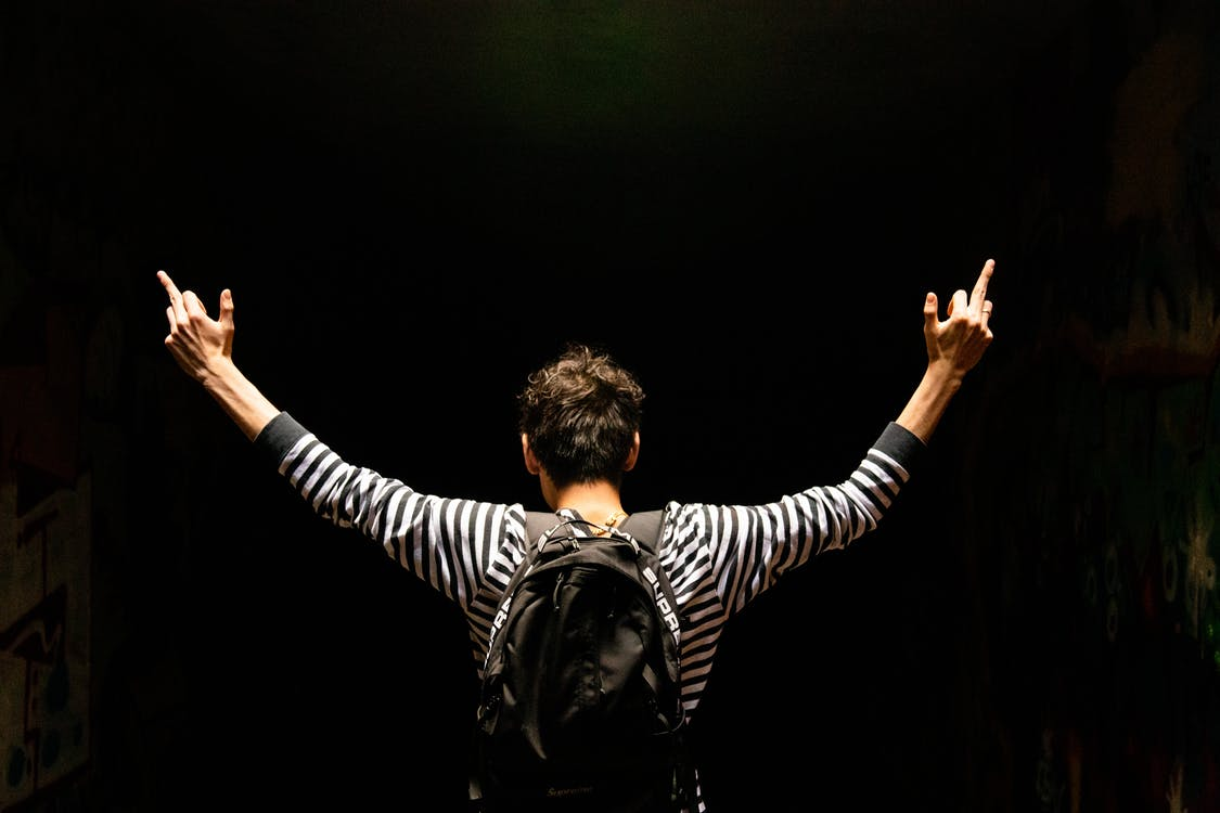Back View Of Man Carrying A Backpack With Arms Raised Doing The Middle Finger