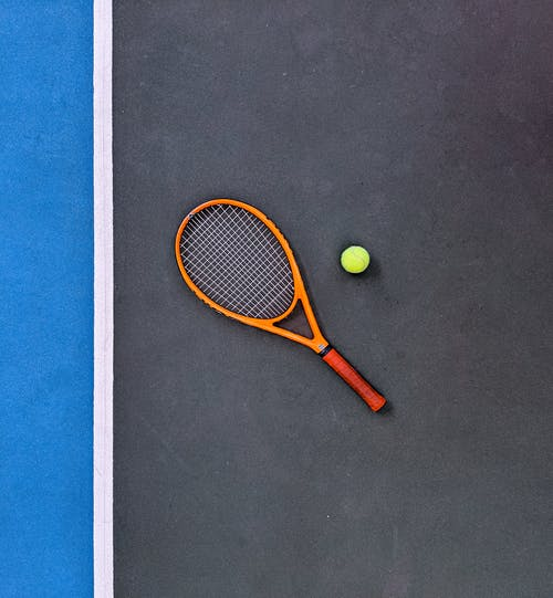 Orange Tennis Racket Beside Green Tennis Ball