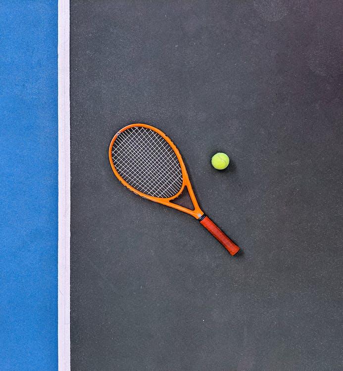 Orange Tennis Racket Beside Green Tennis Ball