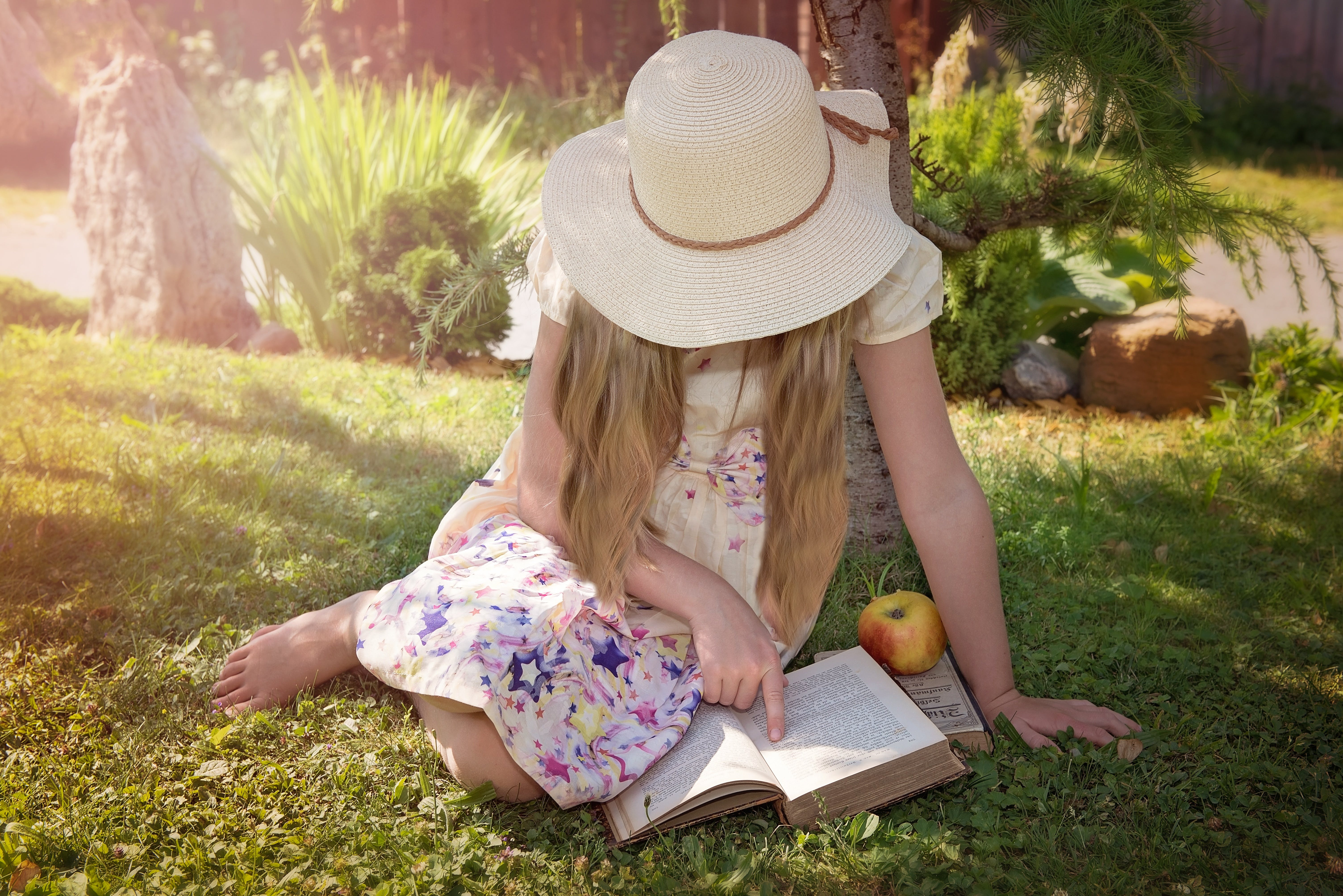 Woman Sitting on Grass While Reading Book