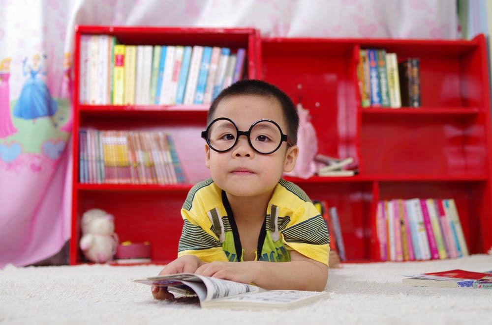 Little boy standing near bookshelf. | Photo: Pexels