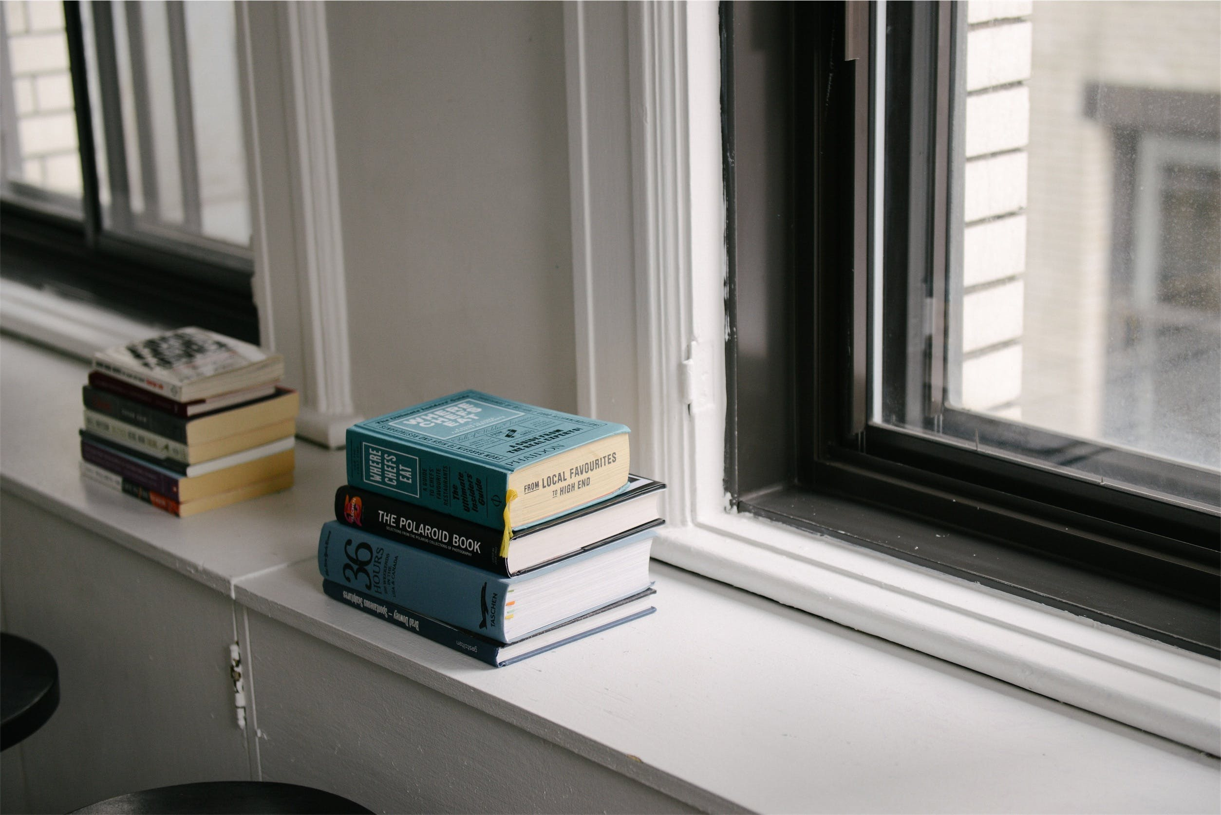 Stack of Books Near Glass Window
