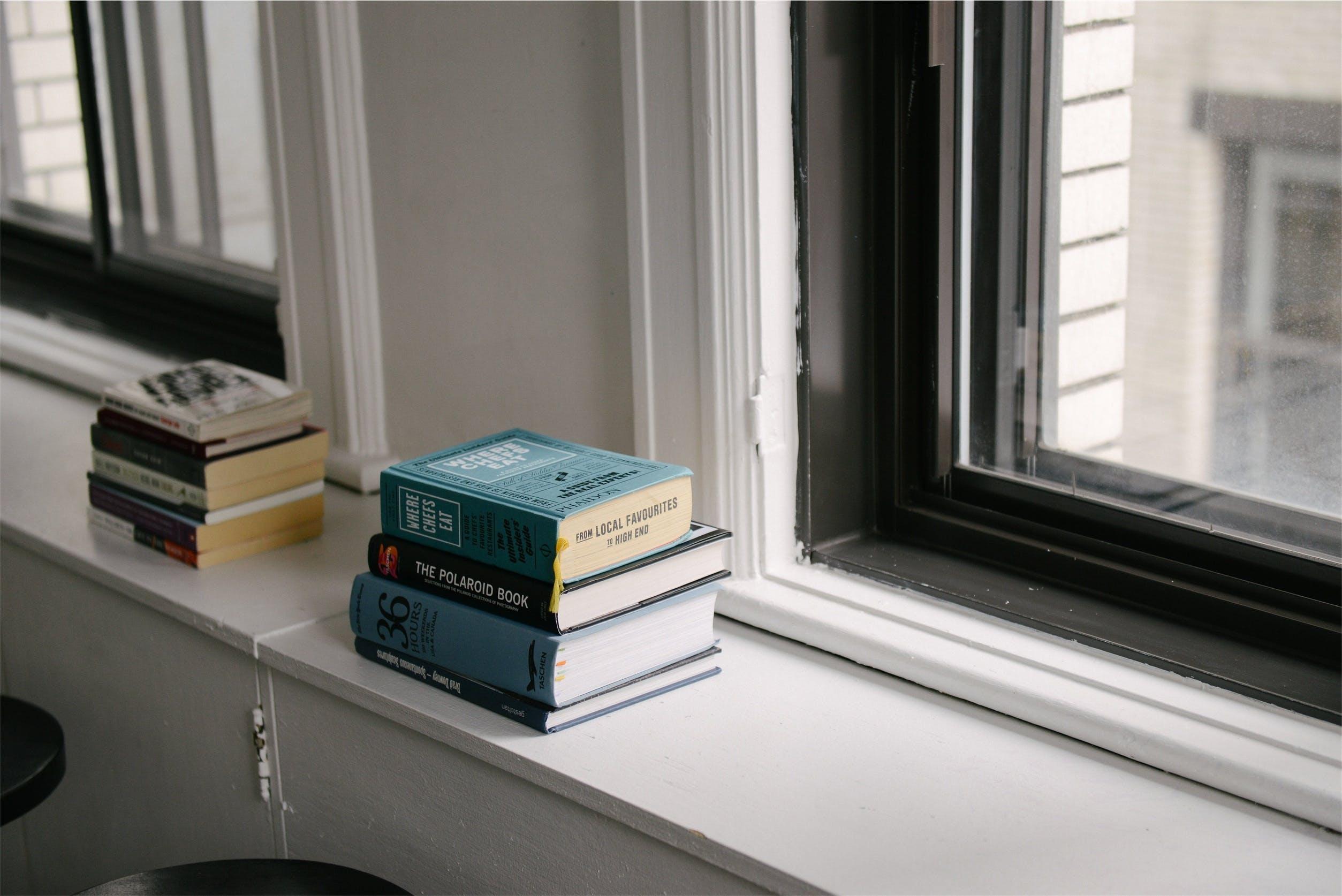 Stack of Books Near Glass Window